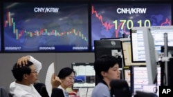 A currency trader watches monitors at the foreign exchange dealing room of the KEB Hana Bank headquarters in Seoul, South Korea, Monday, June 8, 2020. Shares have advanced in Asia Monday after surprisingly strong U.S. jobs figures helped power a…