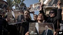 Les partisans de l'ex président Hosni Moubarak tiennent des affiches avec sa photographie près du cimetière où il sera enterré, dans le quartier Héliopolis du Caire, Égypte, le mercredi 26 février 2020.