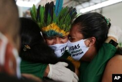 Kerabat menangis selama pemakaman kepala suku Kokama, Messias Martins Moreira, yang meninggal karena COVID-19, di Manaus, Brasil, 14 Mei 2020. (Foto: AP)