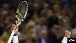 Petenis Spanyol Rafael Nadal mengangkat kedua tangannya setelah mengalahkan petenis Kroasia Marin Cilic di babak keempat Australia Terbuka hari Senin (24/1).