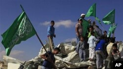 Israeli Arab youths, holding green Islamic flags, stand on the rubble of a mosque, demolished by the Israeli police, in the Bedouin city of Rahat, southern Israel, Sunday, Nov. 7, 2010.