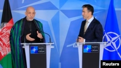 Afghanistan's President Hamid Karzai (L) and NATO Secretary General Anders Fogh Rasmussen make a joint statement before a meeting at NATO headquarters in Brussels, April 23, 2013.