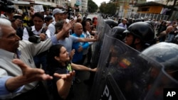 Venezuelan police block a crowd of people gathered to march against the government of President Nicolas Maduro, in Caracas, Venezuela, March 9, 2019.