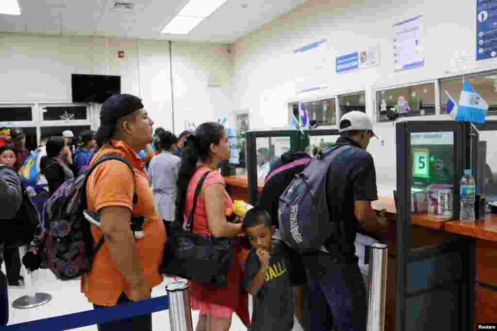 Los hondureños esperan ser registrados por un funcionario de inmigración en la frontera entre Honduras y Guatemala.