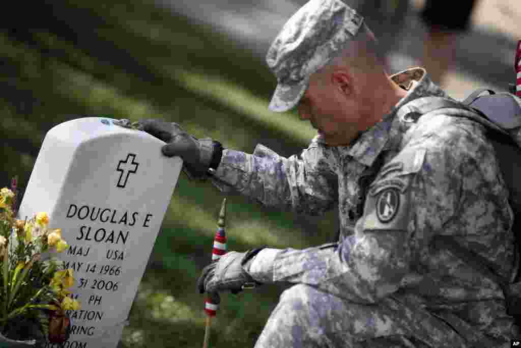 A member of the U.S. Army Old Guard pays his respects at the grave of U.S. Army Major Douglas Sloan, before placing a flag at one of the over 220,000 graves of fallen U.S. military service members buried at Arlington National Cemetery.