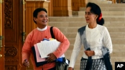 FILE - Myanmar opposition leader Aung San Suu Kyi, right, and Zeyar Thaw, a parliament member of her National League for Democracy party, leave a regular session of Lower House parliament in Naypyitaw, Myanmar, Dec. 3, 2015.