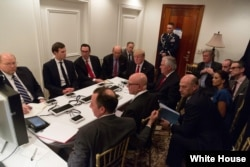 FILE - President Donald Trump receives a briefing on a military strike on Syria from his National Security team on Thursday April 6, 2017, in a secured location at Mar-a-Lago in West Palm Beach, Florida.