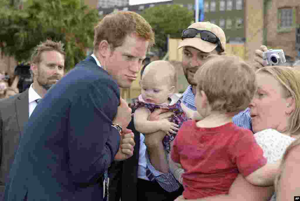 Prince Harry makes a funny face at a young child as he is greeted by a large crowd during the International Fleet Review in Sydney.