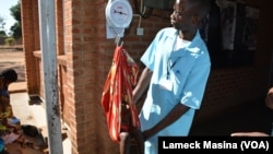 A medical worker weighs a potentially malnutrition child at Mbela health centre in Balaka district, Malawi.