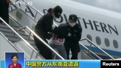 People being deported from Thailand are seen brought off an airplane by police at an unidentified location in China, July 9, 2015, in this still image taken from CCTV video aired on July 11, 2015. CCTV said they were mostly from the country's western Xinjiang region and were attempting to go to Turkey and then to join the Jihad in Syria and Iraq, and 13 of them were terror suspects.