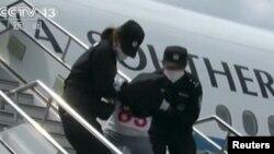 Những người bị trục xuất từ Thái Lan bị đưa ra khỏi một chiếc máy bay của cảnh sát tại một địa điểm chưa xác định ở Trung Quốc ngày 9/7/2015.