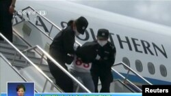 People being deported from Thailand are seen brought off an airplane by police at an unidentified location in China on July 9, 2015 in this still image taken from CCTV video aired on July 11, 2015. CCTV said they were mostly from the country's western, X