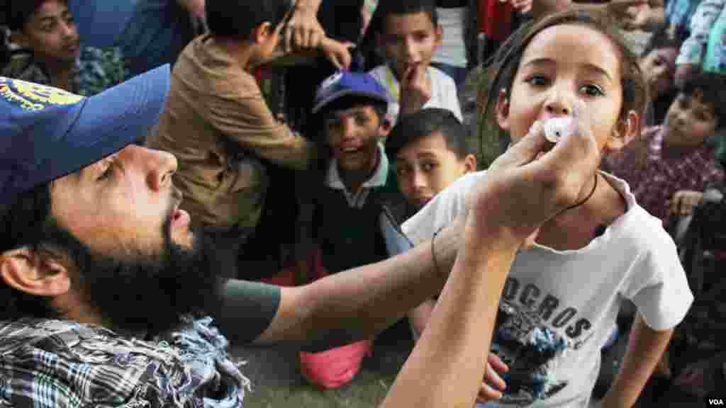 کارمند صحی در حال انداختن قطره واکسین پولیو به دهان یکی از اطفال