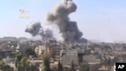 FILE - Plumes of smoke rise from explosions in Deir el-Zour, 450 km northeast of Damascus, Syria, Oct. 29, 2012. Islamic State militants have reportedly launched an attack on government-held areas of the city.