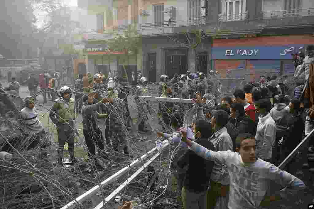 Egyptian protesters stand behind a barbed wire barricade in Tahrir Square in Cairo, November 24, 2011. (AP)