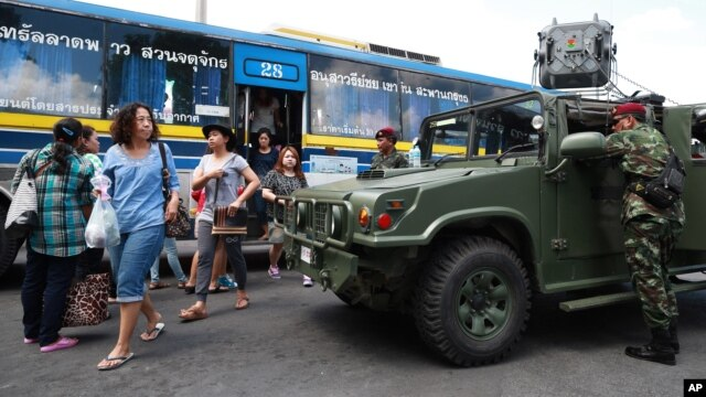 Thai soldiers stand guard near their vehicle as bus passengers walk past in Bangkok's Victory Monument, Thailand, June 8, 2014.