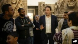 FILE - Stefan Weber, director of the Museum for Islamic Art (C), talks to refugees during a special tour of the complex, in Berlin, Germany, Dec. 16, 2015.