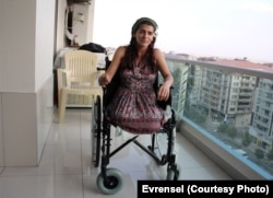 FILE - Lisa Calan on her wheelchair while being interviewed by Turkish reporters at her home five months after the Diyarbakir bombing that cost her two legs, Diyarbakir, Turkey, Oct. 2015.