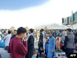 Afghans crowd near the tarmac of the Kabul airport on Aug. 16, 2021, as they try to flee the country.