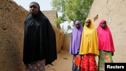 FILE - Amina Usman (L), a 15-year-old student, who was among those who escaped the attack on her school, stands with her sisters in Dapchi, Nigeria, Feb. 23, 2018.