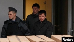 Detained opposition activist Konstantin Lebedev (R, front) is escorted out of a building of the Russian Investigative Committee in Moscow, Oct. 17, 2012.