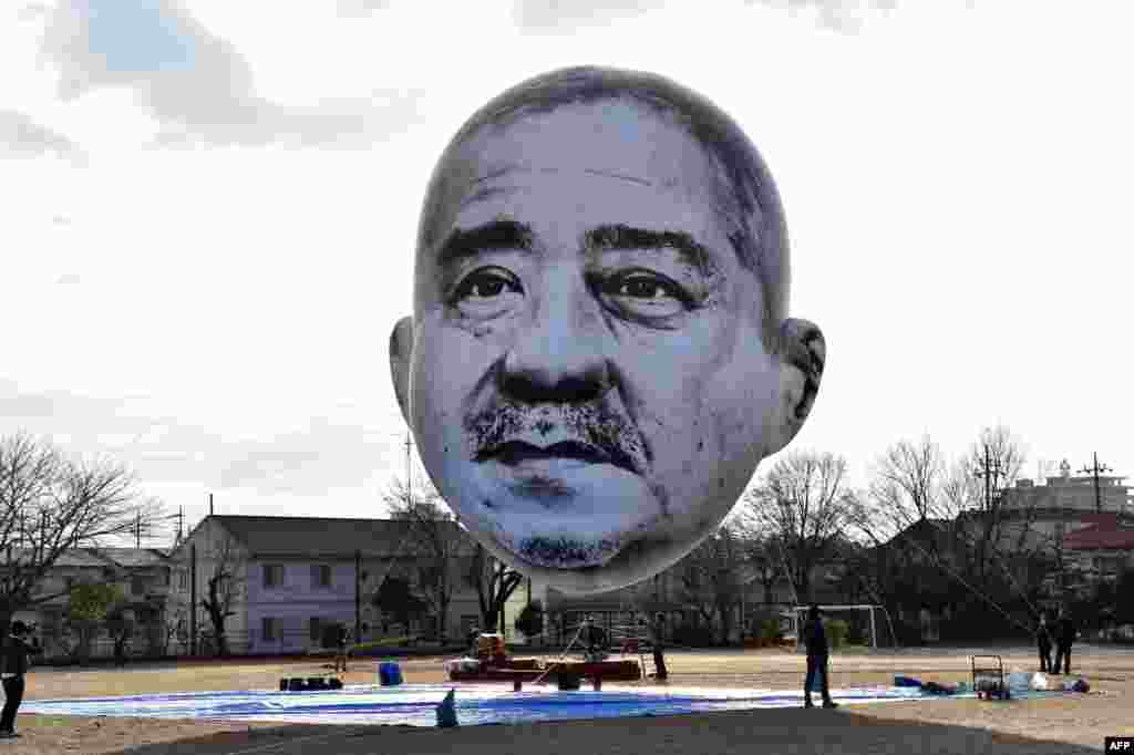 "A large balloon of a face of ""ojisan"", a middle-aged man, floats above the grounds of Nishiki elementary school in Utsunomiya in Tochigi prefecture, 100 km north of Tokyo, Japan. Members of art group ""Me"", meaning ""eye"" in Japanese, and the Utsunomiya Museum of Art launched an art installation ""The Day an Ojisan's Face Floated in the Sky"", a 15-meter by 10-meter face balloon of the depicted man, who was auditioned in the city, looking down on his home town from the sky."