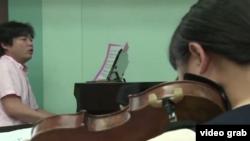 """鋼琴家金哲雄和不願出鏡的小提琴家都是為""""和平音樂會""""演奏的""""脫北者""""。"""