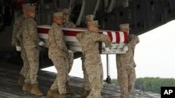 Tim marinir membawa peti jenazah Cpl.Keaton G.Coffey dalam suatu upacara serah terima jenazah di Pangkalan Angkatan Udara Dover, Delaware (26/5). Coffey, salah satu tentara AS yang gugur dalam tugas di Afghanistan.