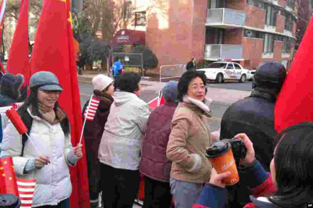 欢迎胡锦涛到访的人们手举中美两国国旗留念