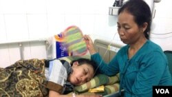Indonesian maid Erwiana Sulistyaningsih is visited by her mother at a hospital on Java, Indonesia. (Ivan Broadhead/VOA)