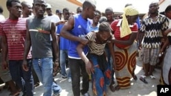 Neighbors help lead away a woman after she collapsed in grief as she visited the local opposition party office where her brother was killed in an overnight attack, in the Yopougon neighborhood of Abidjan, Ivory Coast, 02 Dec 2010
