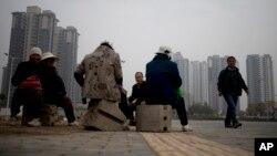 中国陕西西安一处新住宅楼附近一组农民工正在午间休息(资料照片 2013年11月6日)