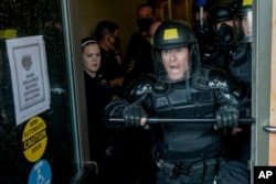 Police try to secure the public safety building from protesters, August 24, 2020, in Kenosha, Wisconsin.