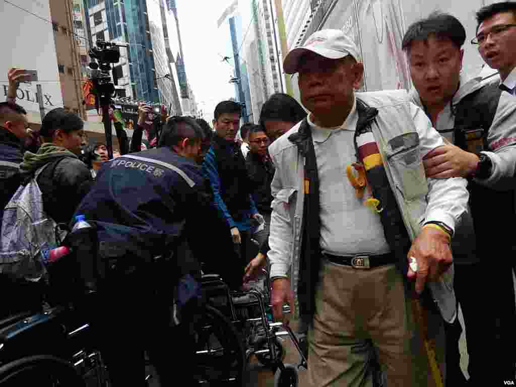 Mr. Wong stands up to be arrested, Hong Kong, Dec. 15, 2014. (Iris Tong/VOA)