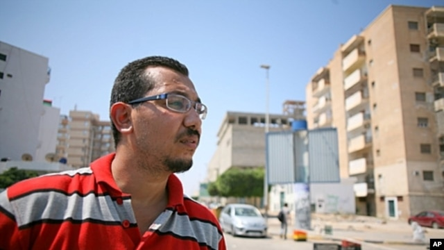 Wahabi Mohammed Yemeni stands at a checkpoint in his neighborhood in Tripoli, August 31, 2011