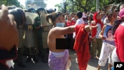 An unidentified female protester tore off her shirt at the demonstration Wednesday as riot police officers looked on.