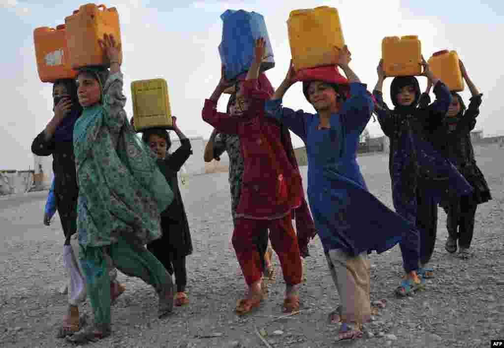 Internally displaced Afghan refugee children carry water in plastic bottles after being filled at a communal pump in Rodat district of Nangarhar province, Afghanistan.