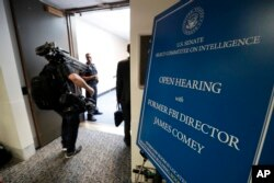 Media enter the hearing room where for former FBI director James Comey will testify before the Senate Intelligence Committee, on Capitol Hill, June 8, 2017, in Washington.