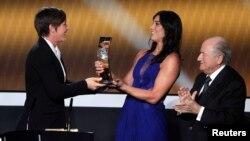 Sepp Blatter, alors à la tête de la FIFA, applaudit alors que Hope Solo, deuxième à partir de la droite, remet un trophée à sa compatriote Abby Wambach lors de la cérémonie de remise des prix FIFA Ballon d'Or 2012, Zurich, 7 janvier 2013