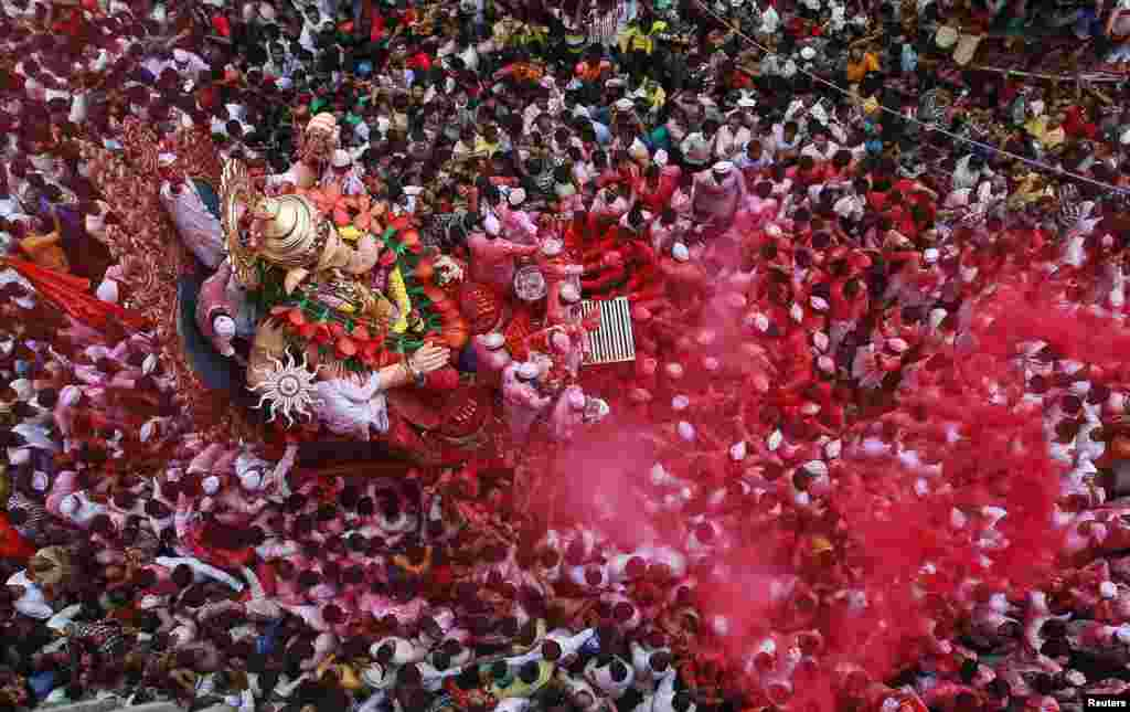 Devotees carry an idol of Hindu elephant god Ganesh, the deity of prosperity, during a procession at the Ganesh Chaturthi festival in Mumbai, India.