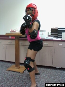 Participants in certified Rape Aggression Defense training wear protective gear to practice repelling an assault.