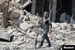 2016年8月27日,叙利亚阿勒颇附近的反政府武装占领区阿尔奈拉伯遭到两次空袭,一名受伤的男子站在一片废墟的建筑物前。