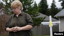 Cư dân Brenda Moe với cây thập tự giá trong sân nhà tưởng niệm những nạn nhân vụ đất chuồi, Darrington, bang Washington, ngày 27 tháng 3, 2014.