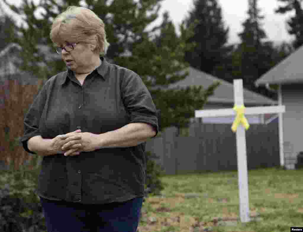 Brenda Moe looks on after placing a cross with a yellow ribbon for victims of the Oso, Washington mudslide on her front lawn in Darrington, Washington, March 27, 2014.