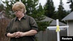برندا مو در حیاط خانه اش صلیبی به یادبود قربانیان برپا کرده و روبان زردی به نشانه امید به یافتن افراد ناپدید شده برآن زده است - دارینگتون ایالت واشنگن، ۲۷ مارس