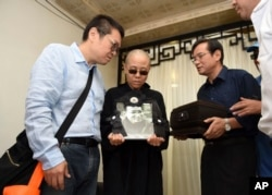 FILE - Liu Xia, wife of jailed Nobel Peace Prize winner and Chinese dissident Liu Xiaobo, holds a portrait of him during his funeral in Shenyang in northeastern China's Liaoning Province, July 15, 2017. Liu has now joined the ranks of those forcibly disappeared.