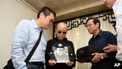 Liu Xia, wife of jailed Nobel Peace Prize winner and Chinese dissident Liu Xiaobo, holds a portrait of him during his funeral in Shenyang in northeastern China's Liaoning Province, July 15, 2017.