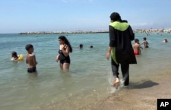 FILE - In this Aug. 4, 2016 file photo made from video, Nissrine Samali, 20, gets into the sea wearing traditional Islamic dress, in Marseille, southern France. The French resort of Cannes has banned full-body, head-covering swimsuits worn by some Muslim wo