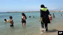 FILE - In this Aug.4 2016 file photo made from video, Nissrine Samali, 20, gets into the sea wearing traditional Islamic dress, in Marseille, southern France. The French resort of Cannes has banned full-body, head-covering swimsuits worn by some Muslim women from its beaches, citing security concerns.