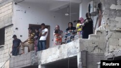 Residents inspect damage after shelling that activists attribute to forces loyal to Syrian President Bashar al-Assad, Raqqa province, May 2, 2013.